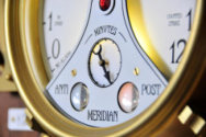 Closeup of steampunk clock face showing minute dial and flickering indicators
