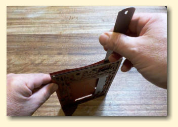To ensure the bottom tape is secure, repeatedly push a ruler down inside the pocket against the table