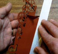 Line the ruler up with the fold marks on the slotted tab